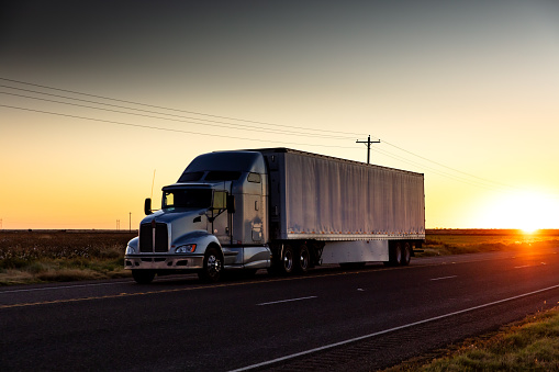Semi-truck on a lonely highway in Texas at sunset.