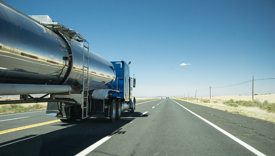 truck with a silver tank trailer passing a passenger car on a highway in Texas