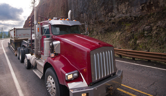 Classic red American semi truck with step down semi trailer transporting road work transportation equipment on meandering mountain road